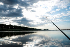 Fishing on sunrise. Fisherman sport hobby fishing rod or spinning reel on the river. Fishing on sunrise. beautiful sunrise on the river is reflected in water Royalty Free Stock Photos