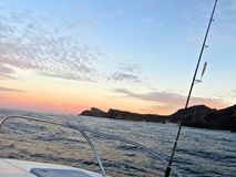 Fishing Sunrise. View off the back of a tuna fishing boat overlooking the South African coast and the sunrise on the ocean with a reel in the foreground royalty free stock images