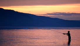 Fishing at sunset. Sunset over Jackson lake with fisherman silhouetted in foreground, Grand Teton National Park, Wyoming, U.S.A royalty free stock photography