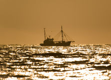 Fishing at sunset. A fishing boat at sunset, with the sun reflection on the sea water Stock Photos