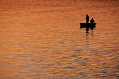Fishing at sunset. Two fishermen on small boat fishing at sunset on Poraj lake, Poland Royalty Free Stock Photos