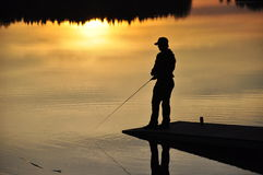 Fishing At sunset. A silhouette of a ficherman as the sunset on lower Royalty Free Stock Image