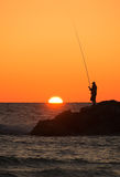 Fishing at sunset. Fisherman silhouette against the background of a picturesque sunset over the sea Royalty Free Stock Image