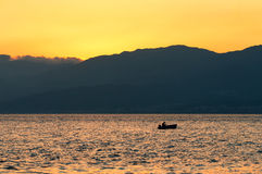 Fishing at sunset. A fisherman, fishing with his boat at sunset on the Strait of Messina Stock Photo