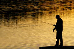 Fishing At Sunset. A silhouette of a fisherman as the sun sets on lower Royalty Free Stock Photos