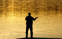 Fishing At sunset. A silhouette of a ficherman as the  sunsets on lower Stock Photography