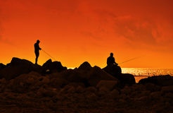 Fishing at sunset. A fishermans in sunset at the coast Royalty Free Stock Image