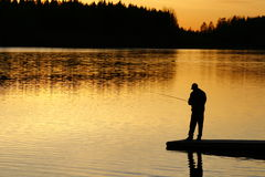 Fishing At Sunset. A silhouette of a fisherman as the sunsets on lower Stock Photo