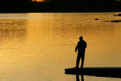 Fishing At sunset. A silhouette of a fisherman as the sunset on lower Royalty Free Stock Photo