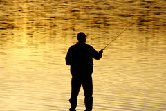 Fishing At sunset. A silhouette of a fisherman as the sunset on lower Royalty Free Stock Images