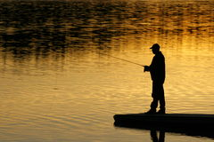 Fishing At sunset. A silhouette of aficherman as the sunset on lower Stock Photos