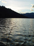 Fishing at sunset. Fishing in a mountain lake at sunset Stock Photo