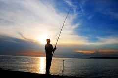 Fishing at sunset. Silhouette of fisherman at sunset stock photography