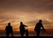 Fishing at sunset. Silhouette of three fishermen with beautiful sunset background Stock Images