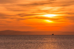 Fishing on sunset. A fishing boat passes the sea at the time of sunset Royalty Free Stock Photo