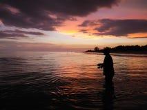 Fishing at Sunset. A fisherman at sunset fishing the beach of Sanibel Florida royalty free stock image