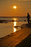 Fishing at sunset. Fisherman silhouette on a mole at sunset royalty free stock photo