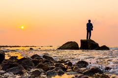 Fishing at sunset. Fisherman standing on a rock at dawn sky background Royalty Free Stock Photography