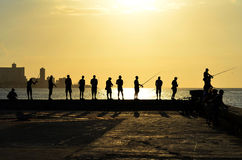 Fishing during the sunset in Havana (Cuba). Every day, before sunset, dozens of fishermen meet in the Malecon (Havana's harbour). Here you can observe some of Royalty Free Stock Photography