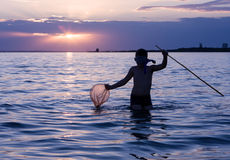Fishing at sunset. Little boy fishing in the sea at sunset stock photography