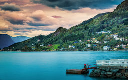 Fishing at sunset in Norway. Cloudy sunset in Norway with tourist fishing in a scenic fjord Royalty Free Stock Photo