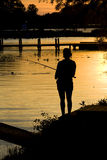 Fishing sunset silhouette. Women fishing on a shoreline at dusk Stock Photos