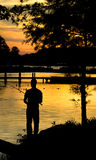 Fishing sunset silhouette. Man fishing on shoreline at dusk during a sunset Royalty Free Stock Images
