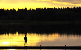 Fishing At sunset. A silhouette of a ficherman as the sunset on lower Royalty Free Stock Photo