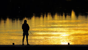Fishing At sunset. A silhouette of a ficherman as the sunset on lower Royalty Free Stock Photos