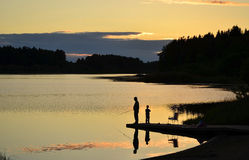 Fishing At sunset. A silhouette of a ficherman and his son as the sunset on lower Royalty Free Stock Photo