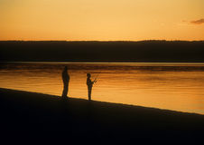 Fishing at sunset, Yellowstone, Wyoming. Father and son fishing at sunset at Yellowstone Lake, Yellowstone National Park, in Wyoming, United States Stock Photos
