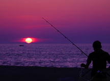 Fishing at Sunset. Young man untangles his line while fishing off the Holland State Park pier Royalty Free Stock Photo