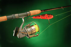Fishing tackle. Composition with rod, lure and reel on the green background Stock Photography