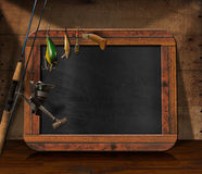 Fishing Tackle with Empty Blackboard. Empty blackboard with fishing tackle and folding knife on a wooden table and wooden wall Royalty Free Stock Photos