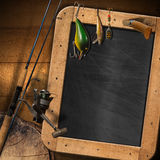 Fishing Tackle with Empty Blackboard. Empty blackboard with fishing tackle and folding knife on a wooden wall Stock Photo