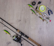 Fishing tackle - fishing spinning, hooks and lures on light wooden background. Top view royalty free stock photography