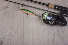 Fishing tackle - fishing spinning, hooks and lures on light wooden background. Royalty Free Stock Photography