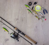 Fishing tackle - fishing spinning, hooks and lures on light wooden background. Royalty Free Stock Image
