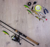 Fishing tackle - fishing spinning, hooks and lures on light wooden background. Royalty Free Stock Images