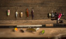 Fishing tackle - fishing spinning, hooks and lures on light wooden background.Top view. Royalty Free Stock Image
