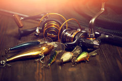 Fishing tackle - fishing spinning, hooks and lures on wooden bac. Fishing tackle - fishing spinning, hooks and lures on darken wooden background Royalty Free Stock Photography