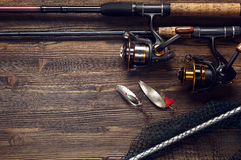 Fishing tackle - fishing spinning, hooks and lures on wooden bac. Fishing tackle - fishing spinning, hooks and lures on darken wooden background.Top view Stock Photography