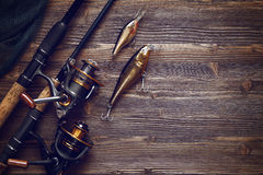 Fishing tackle - fishing spinning, hooks and lures on wooden bac. Fishing tackle - fishing spinning, hooks and lures on darken wooden background.Top view Stock Photo