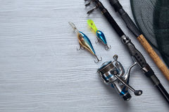 Fishing tackle - fishing spinning, hooks and lures on wooden bac. Fishing tackle - fishing spinning, hooks and lures on light wooden background.Top view Royalty Free Stock Images
