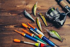 Fishing tackle - fishing spinning, hooks and lures on wooden background royalty free stock photos