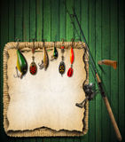 Fishing Tackle Green Wood Background. Green wooden background with fishing tackle, knife and wicker basket Royalty Free Stock Photo