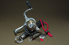 Fishing tackle lying on a dark background. Fishing reel with lures and capture on a dark background Stock Images