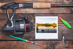 Fishing tackle and a photo of successful fishing Royalty Free Stock Photo