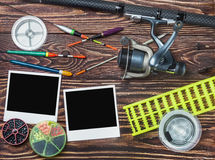 Fishing tackle and photoframe. On wooden table Royalty Free Stock Photo