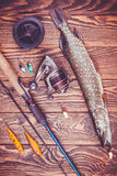 Fishing tackle and pike on a wooden table Stock Photography